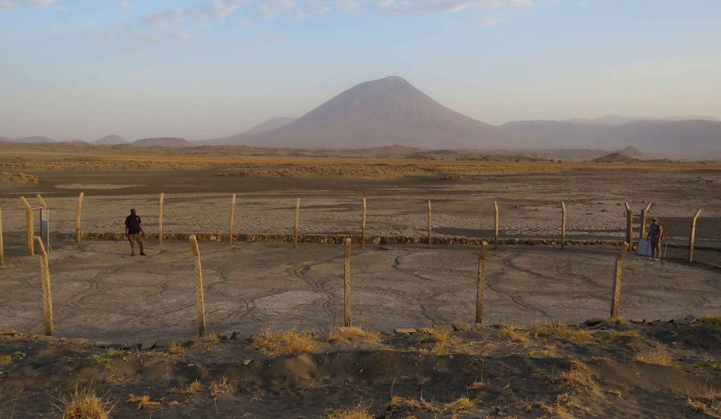 As these people walked, their feet squished into an ashy mudflat produced by an eruption of Ol Doinyo Lengai volcano, which even today (above) is still active and looms over the site of the footprints.