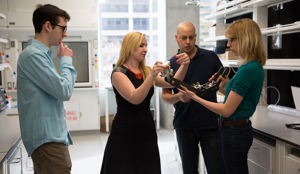 Leftwich (second from left) and her colleagues examine a robotic sea lion flipper, which is used to replicate and study the motions of a real sea lion flipper.