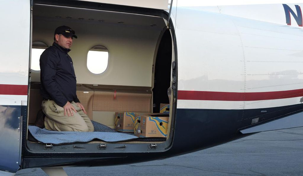 A shipment of sea turtles—in banana boxes—being loaded into a  Pilatus PC-12.