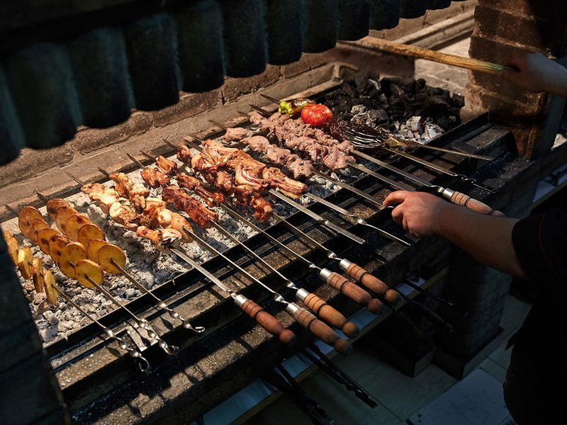 A cook works on khorovats skewers at Taron Restaurant in Yerevan.