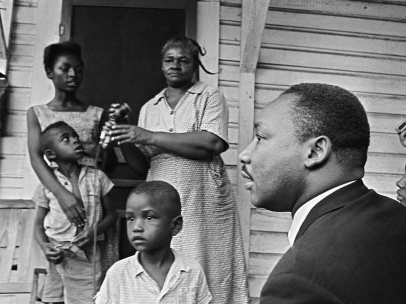 Dr. Martin Luther King Jr. , chats with African-Americans during a door-to-door campaign in 1964.