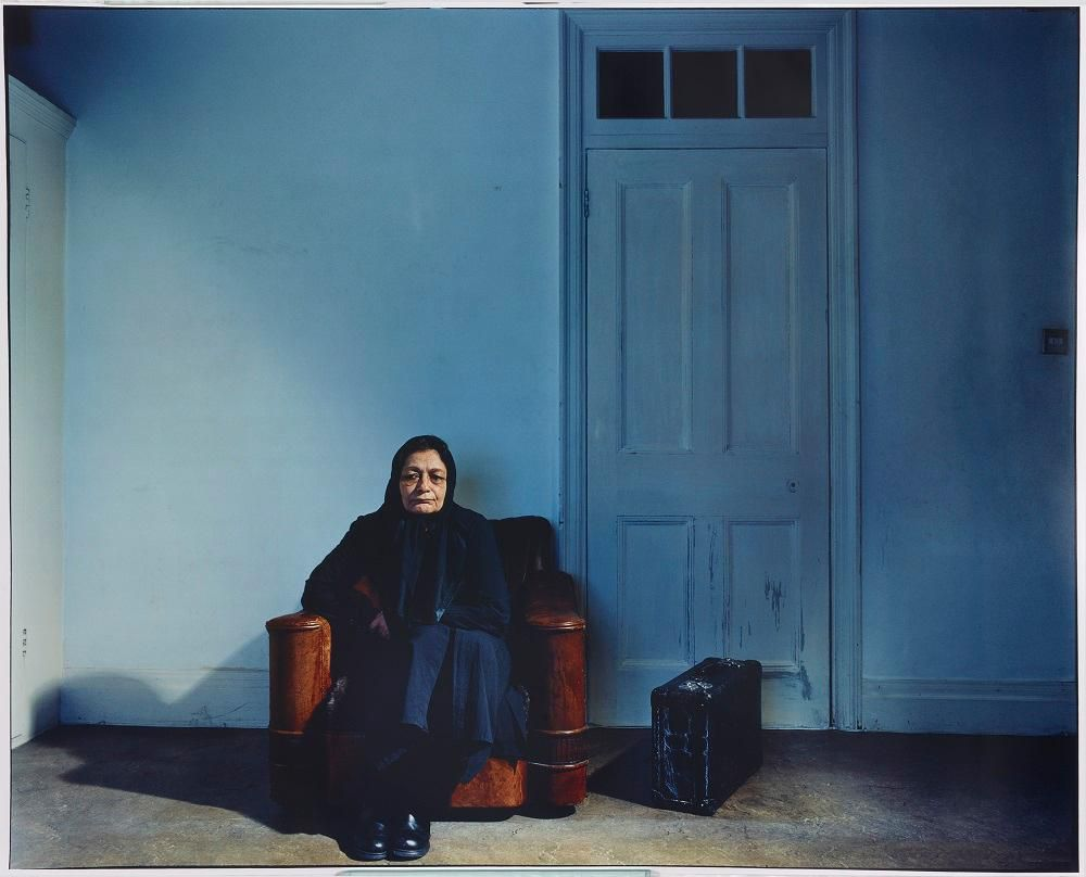 Seated woman with suitcase by door