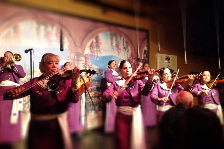 An all women Mariachi band, outfitted in matching purple and white traditional clothing, performs together in front of a painted mural depicting an archway facing the ocean.