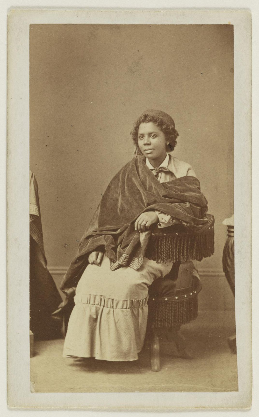 A sepia-toned image of a woman sitting in a chair, wrapped in a shawl.