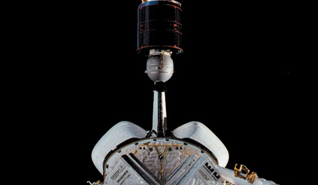 A commercial satellite pops up from the shuttle's cargo bay. Later its rocket engines will fire to place the satellite in orbit.