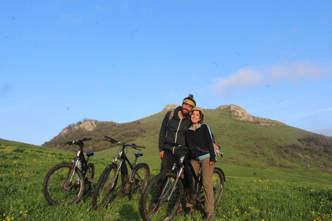 On a sunny day, two friends stand next to each other holding bicycles in an open field.