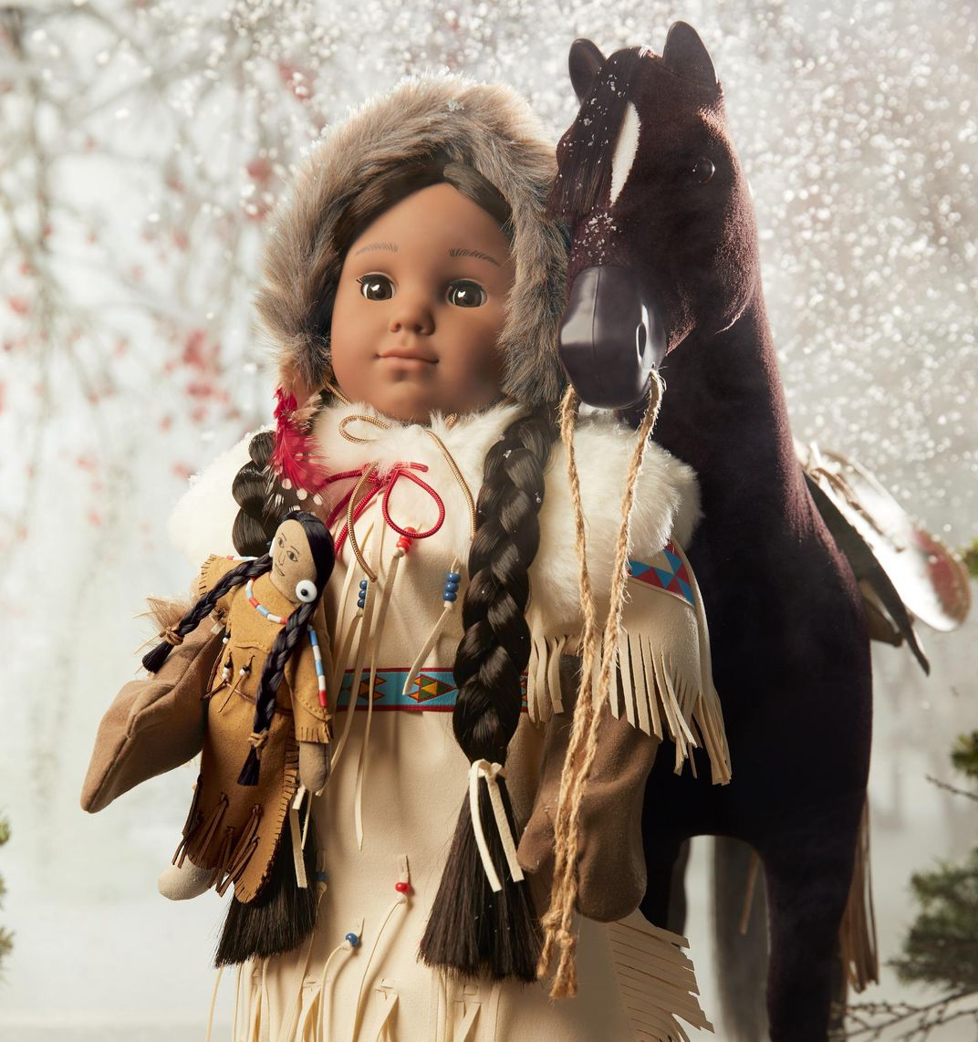 Kaya doll poses with her horse in front of a snowy backdrop