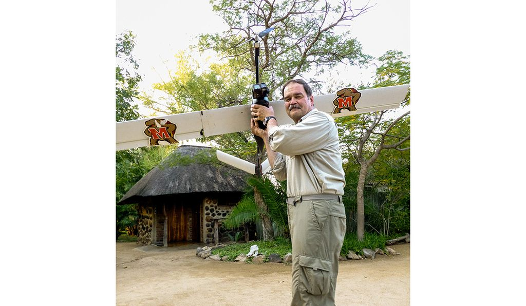 Tom Snitch, left, of the University of Maryland demonstrates a drone that uses a predictive algorithm to fly where poachers are most likely to be. In trial runs in South African wildlife parks, the system dropped poachings from 12 to 18 per month to zero.