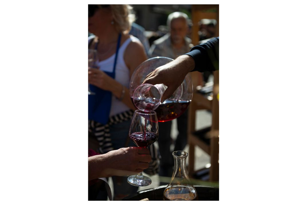 One person pours a glass of wine into a wine glass held by another person.