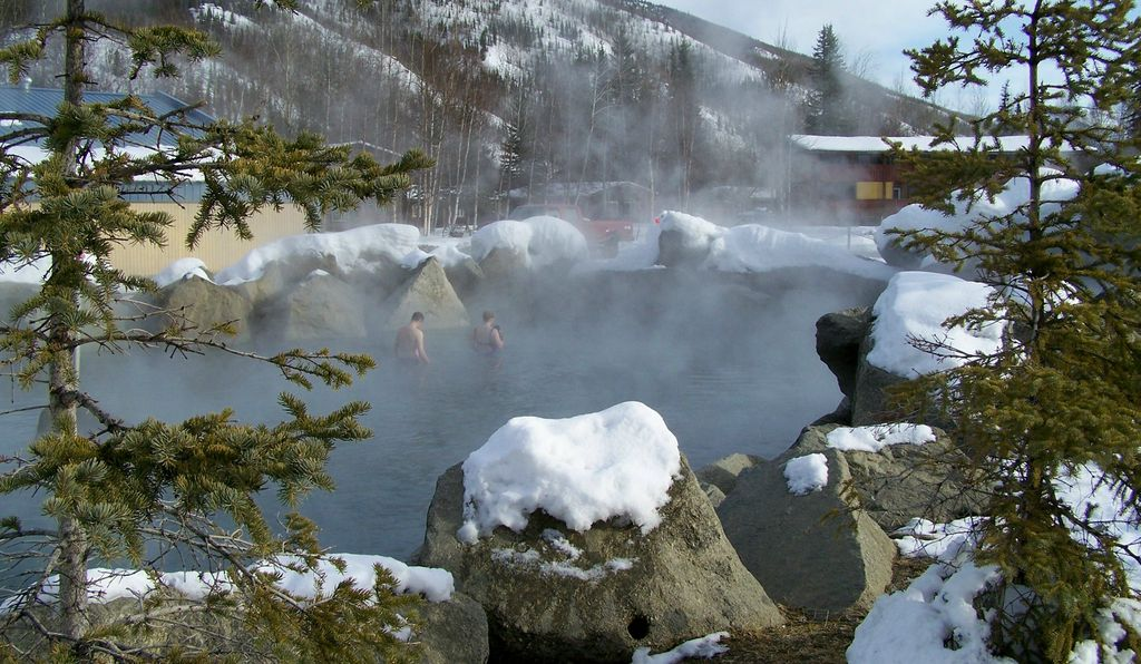 A couple through steam enjoying the natural outdoor rock lake.