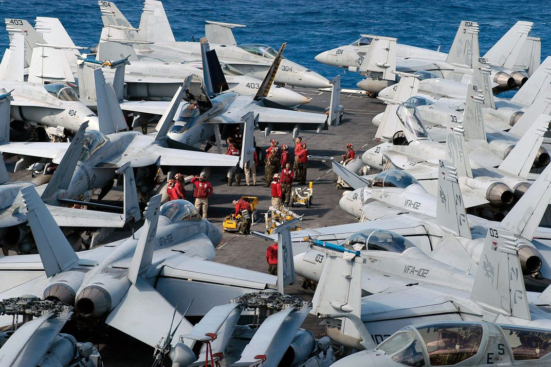 men in red shirts loading hornets on carrier