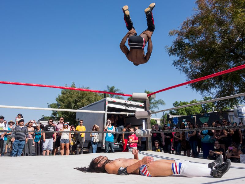 A wrestler does a backflip off the ropes of a wrestling ring in an attempt to defeat an opponent.