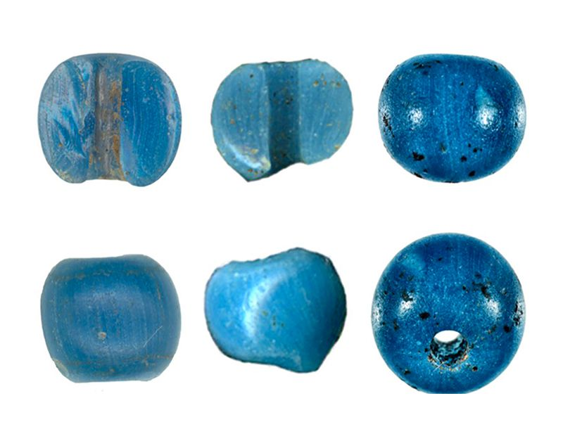 Six small bright, light blue beads, some all the way intact and some halved to reveal their small middle hole