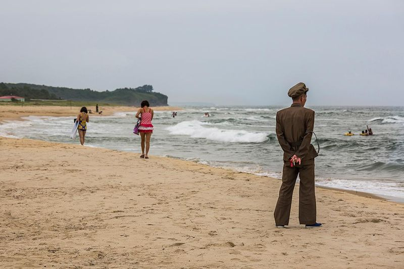 A Man In Military Uniform Watches Beach Goers Near Wonsan East Coast North Korea Tariq Zaidi Zuma Press