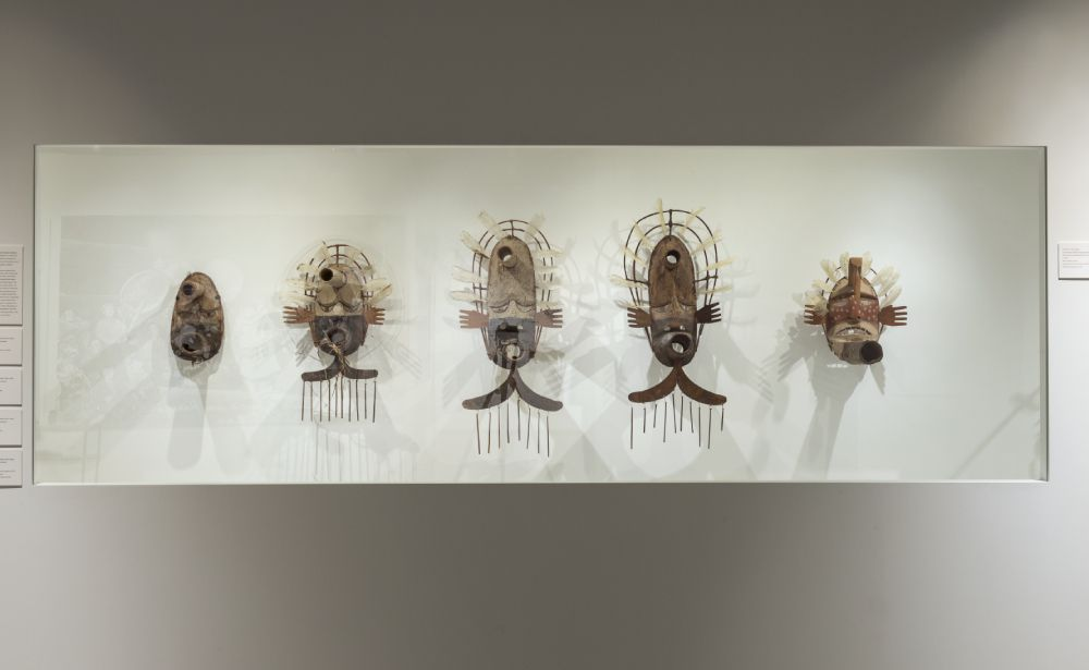 Five masks hanging side-by-side on a white wall.