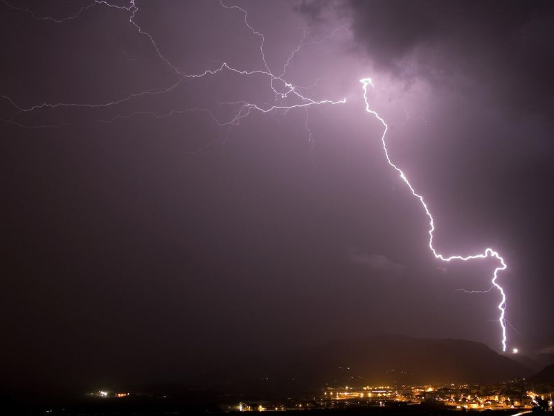 A lightning bolt shoots across the sky at night over a town with yellow lights