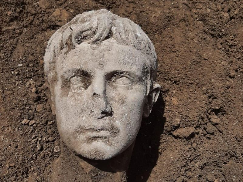 A white marble head covered partially in dirt; rests on a dirt ground next to someone's shoe