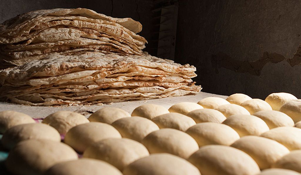Baked lavash rests next to mounds of dough ready for baking.