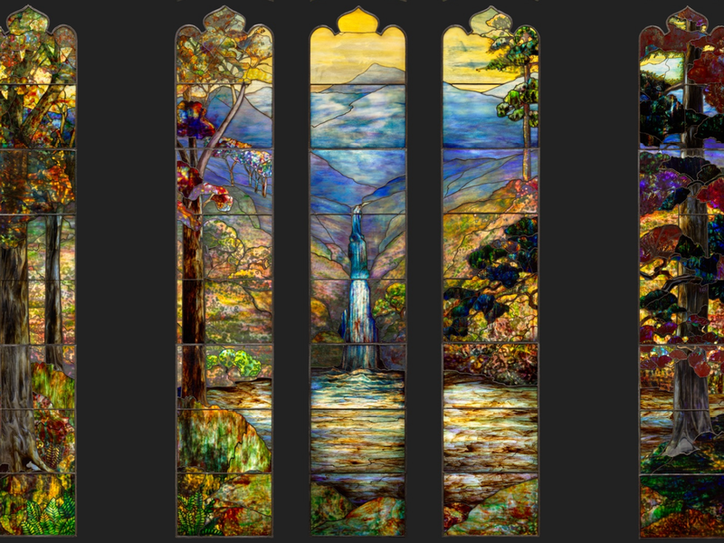 Five thin panels of stained glass, two on either side and three grouped closely together, depict a colorful landscape with blue mountain in the background and a waterfall flowing into a yellow green pond