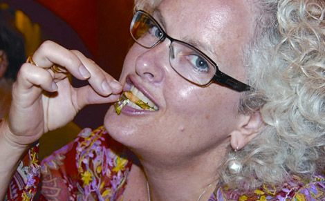 Janice Waugh eating a cricket on the Riviera Maya, Mexico