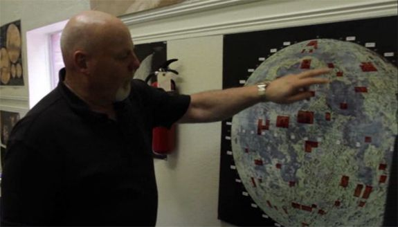 Dennis Hope stands next to a map of the Moon, showing (in red) all the plots of land he's sold.