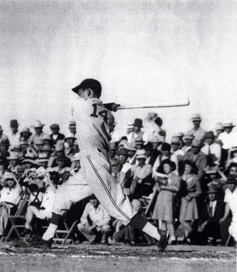 Black and white photo of Testuo Furukawa swinging a baseball bat in front of a small crowd
