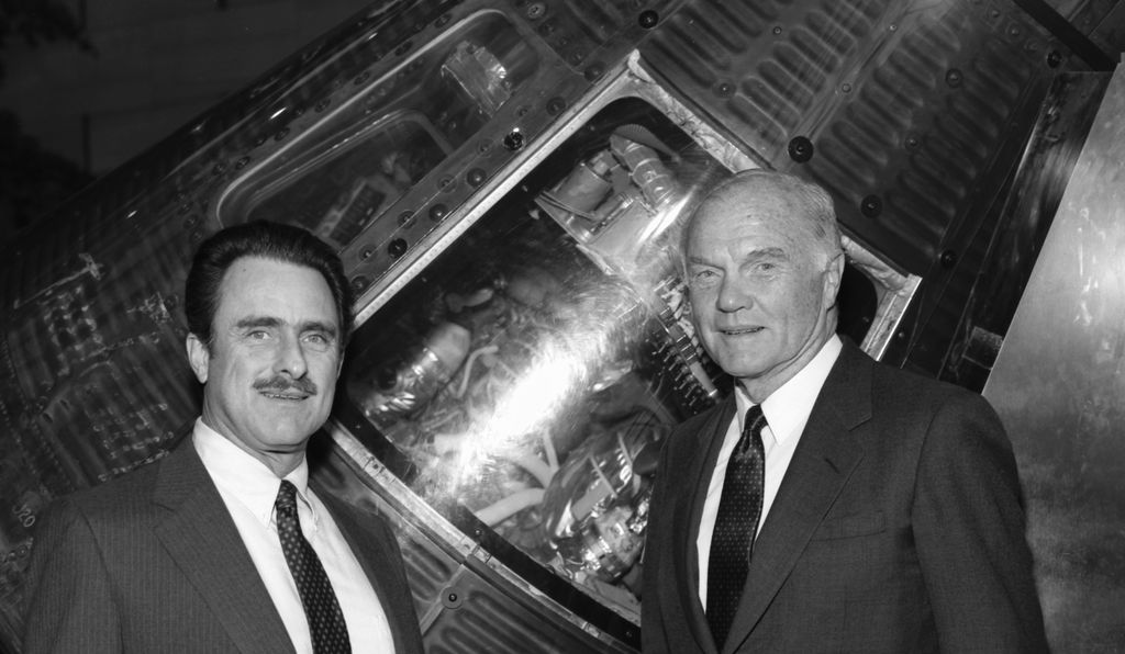 John Glenn (right) stands in front of the Mercury Friendship 7 spacecraft that took him into orbit at a 1987 press conference honoring the 25th anniversary of his mission.