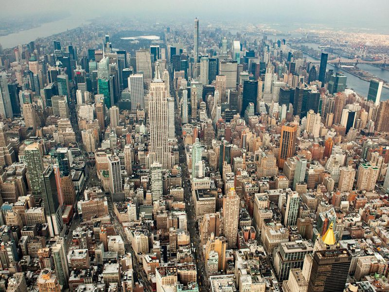 An aerial photograph of New York City. There are endless rows of skyscrapers and shiny buildings, stretching back to the horizon.