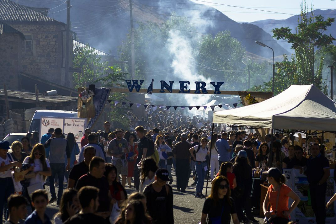 """At the Areni Wine Festival, people stand gathered in a large group under a banner reading """"winery."""""""