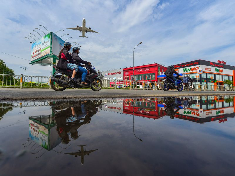 An aircraft preparing for landing at Tan Son Nhat International Airport flies over the streets of Ho Chi Minh City.