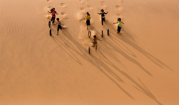 Children playing with tires on the sand dune.