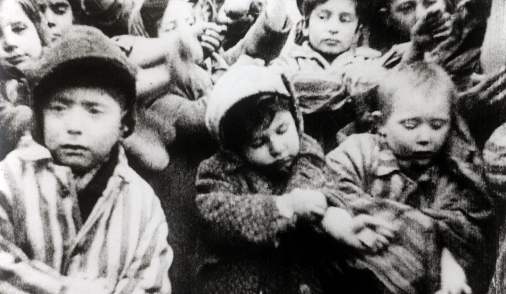 Child survivors of Auschwitz show a Soviet photographer their tattooed arms in February 1945.