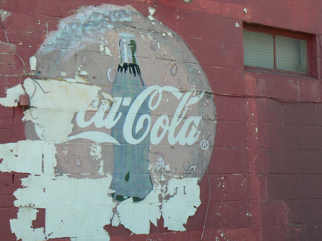 An old Coke a Cola ad on the side of small convenience store