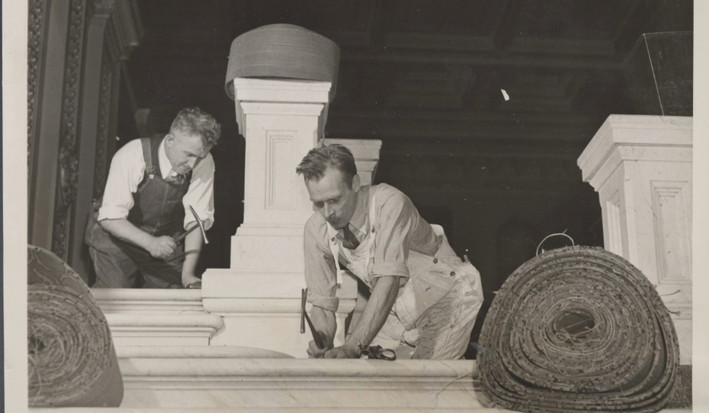 Workers install new carpet in the House rostrum in the 1930s.