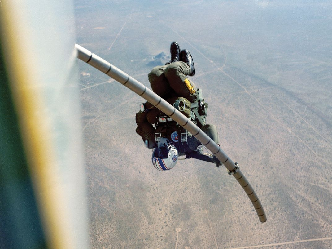 Navy parachutist slides down a telescoping pole