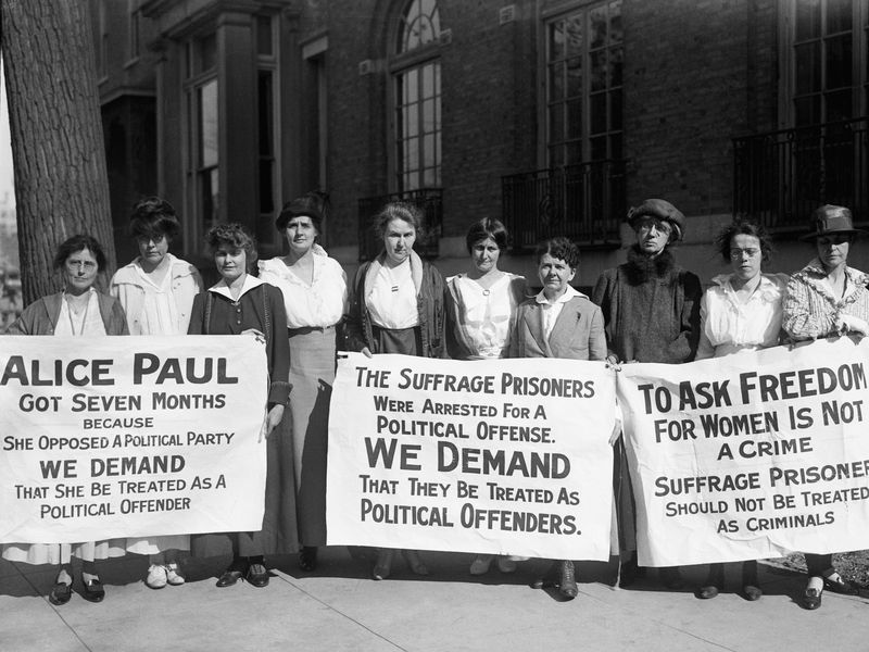 suffragists holding signs demanding political prisoner treatment for Alice Paul