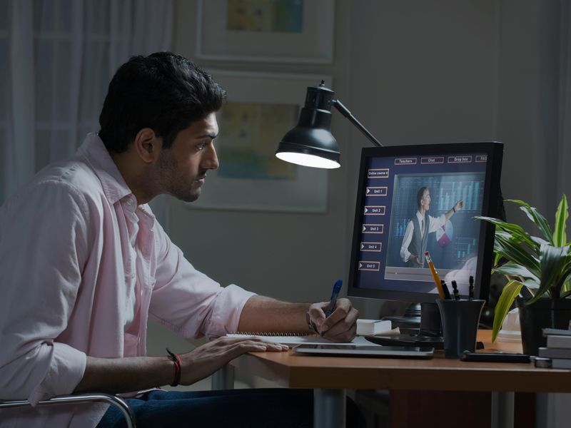 Stock photo image of a man watching a generic lecture on a desktop computer screen