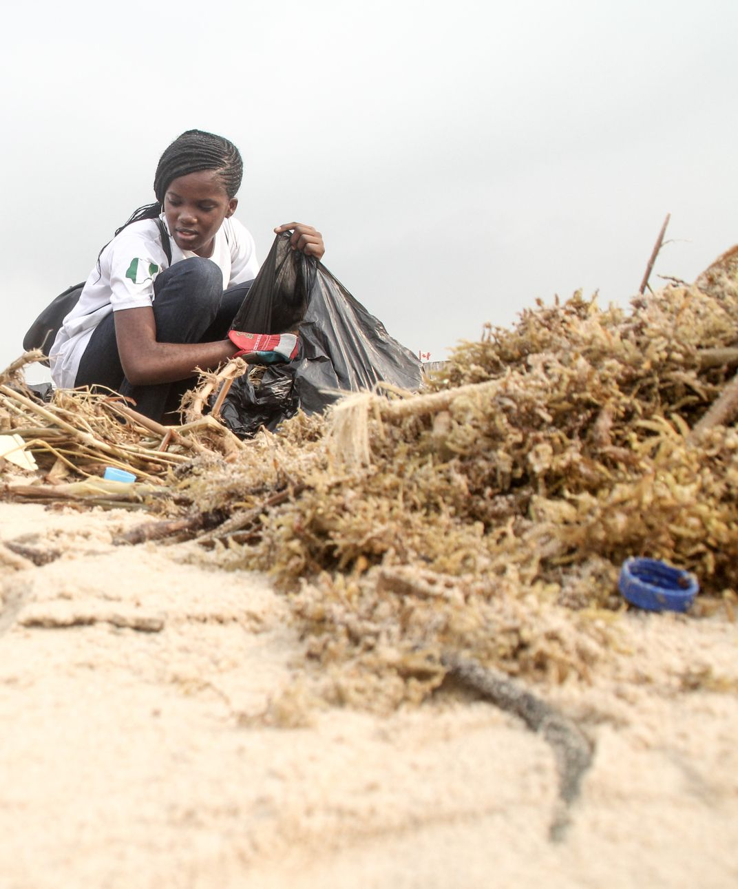 girl cleans up plastic trash on a beach