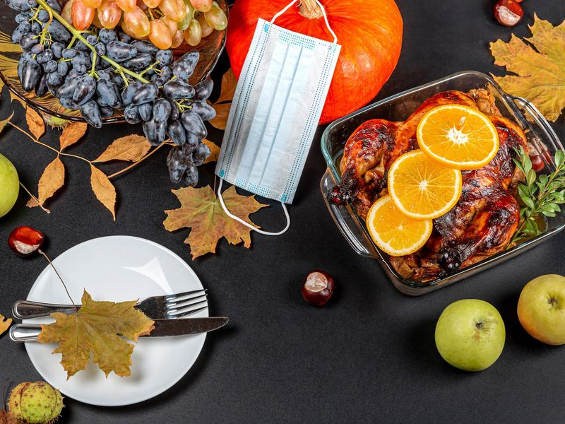 A photograph of a table taken from above. Table has dried leaves, a white plate with a fork and knife, a roasted chicken with orange slices in a glass tray. There is a a pumpkin with a blue disposable mask draped over the stem at the top of the image.