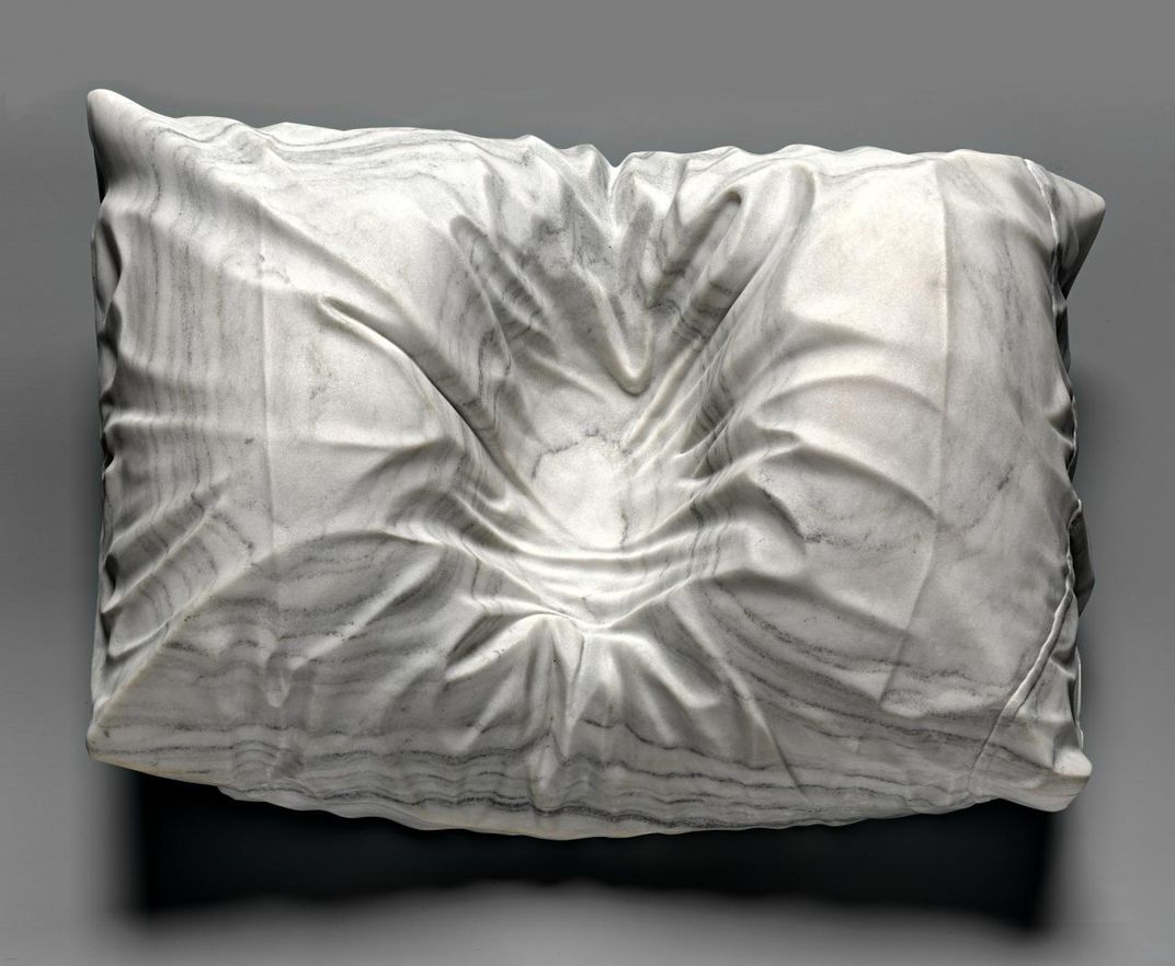 A photograph of a marble pillowcase with an indention where a head was.