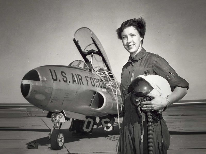 A photograph of a woman dressed to fly a jet, holding a helmet. The jet behind her has the top open and is labeled