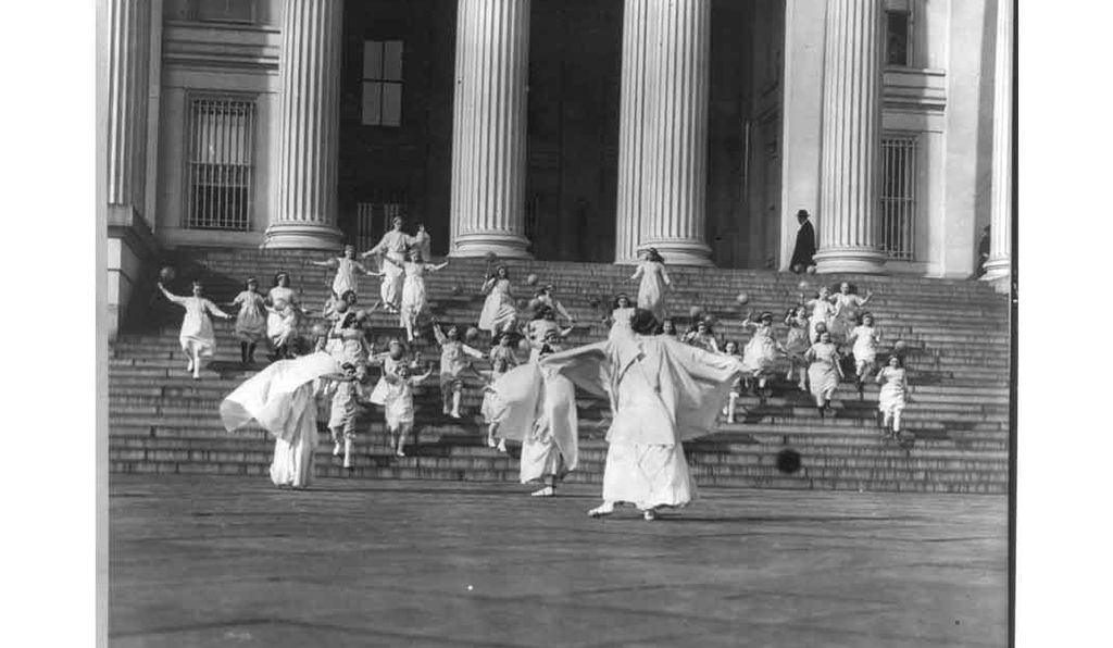 Suffragettes and young girls carrying balloons on the steps of the U.S. Treasury, 1913