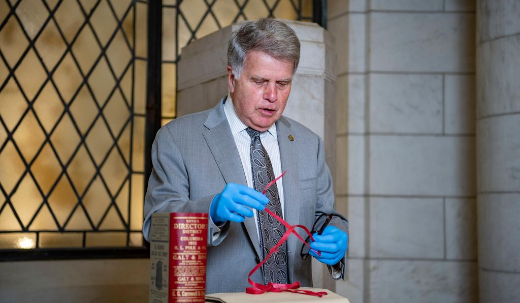Archivist of the United States David S. Ferriero displays the red tape used to bind documents in the time capsule.