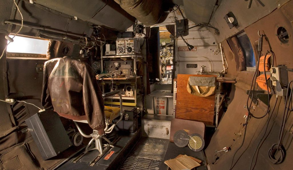 Inside the aircraft's forward fuselage, looking towards the cockpit, is a view of the navigator position and the radio on the left.
