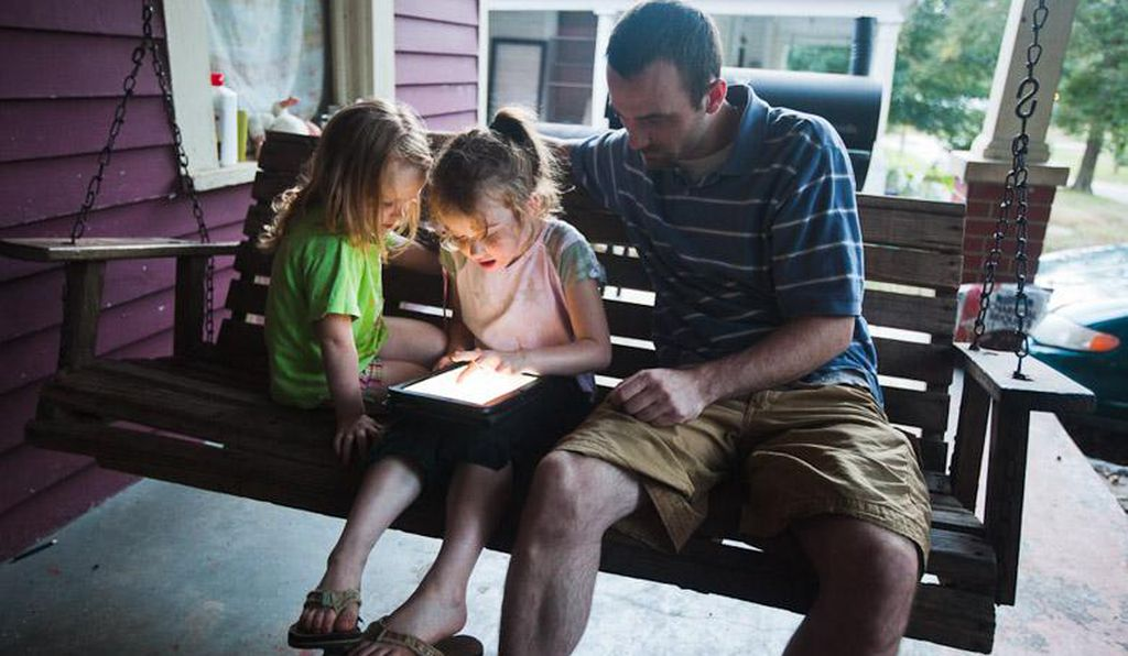 Roanoke kindergartener Gracie Williams, at home with her sister and father, Carl, tinkers with an experimental tablet computer containing specially designed educational apps.