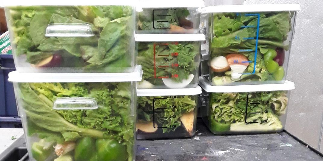 Plastic bins full of lettuce and chopped fruits and vegetables stacked on a table.