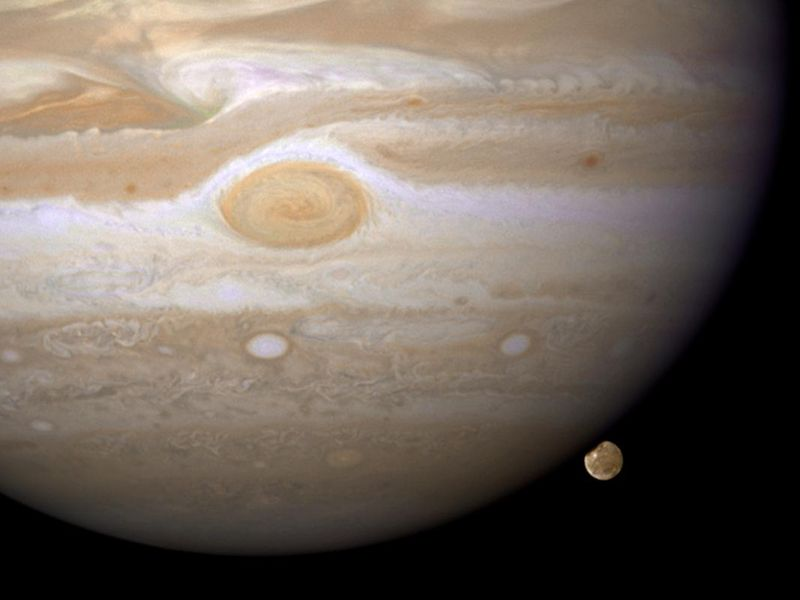 Spanning most of the image is the planet Jupiter, its red spot centrally featured. In the lower right, its largest moon Ganymede peaks from behind the planet.
