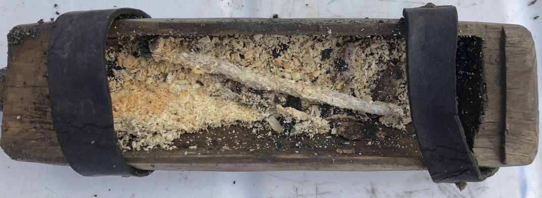 An interior view of the rectangular box, which is full of what resembles a long thin tapered candle, surrounded by crumbled bits of yellowed beeswax