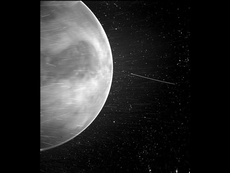 A letterboxed image with NASA's new Venus placed vertically at the center. Half of the planet is positioned on the left part of the picture with celestial objects zooming by and stars in the background