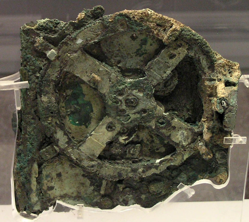 A rusted, green, degraded gear in the shape of an X with a circle around it, on display in a museum